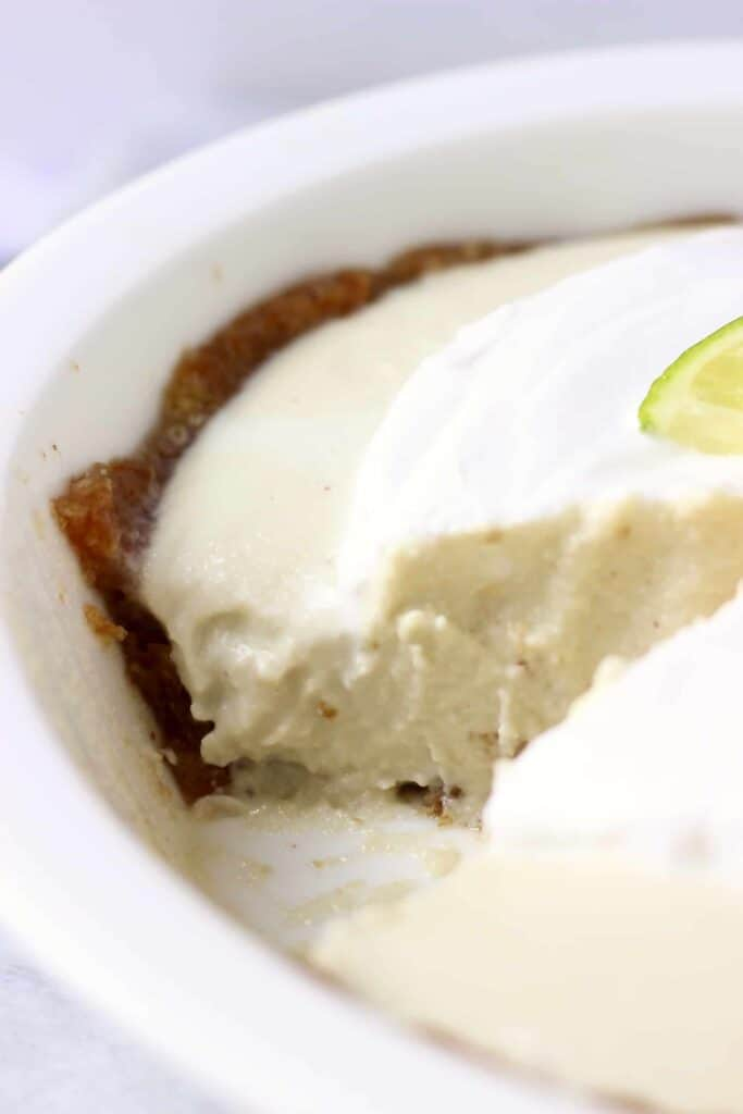 Photo of a pie topped with cream and a lime slice in a pie dish with a slice taken out of it