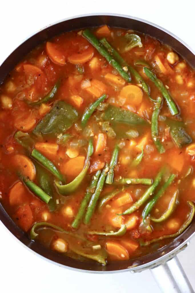 Photo of chickpeas and vegetables in a tomato stew cooked in a saucepan