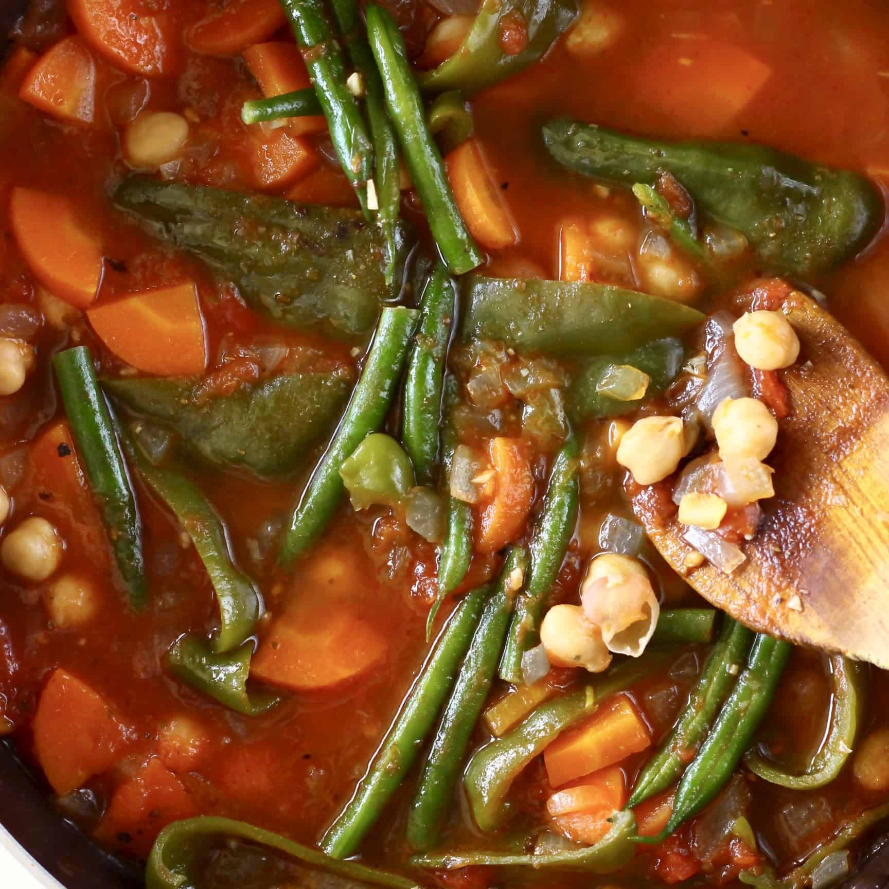 Photo of chickpea and vegetable tomato stew in a saucepan with a wooden spatula holding up some chickpeas