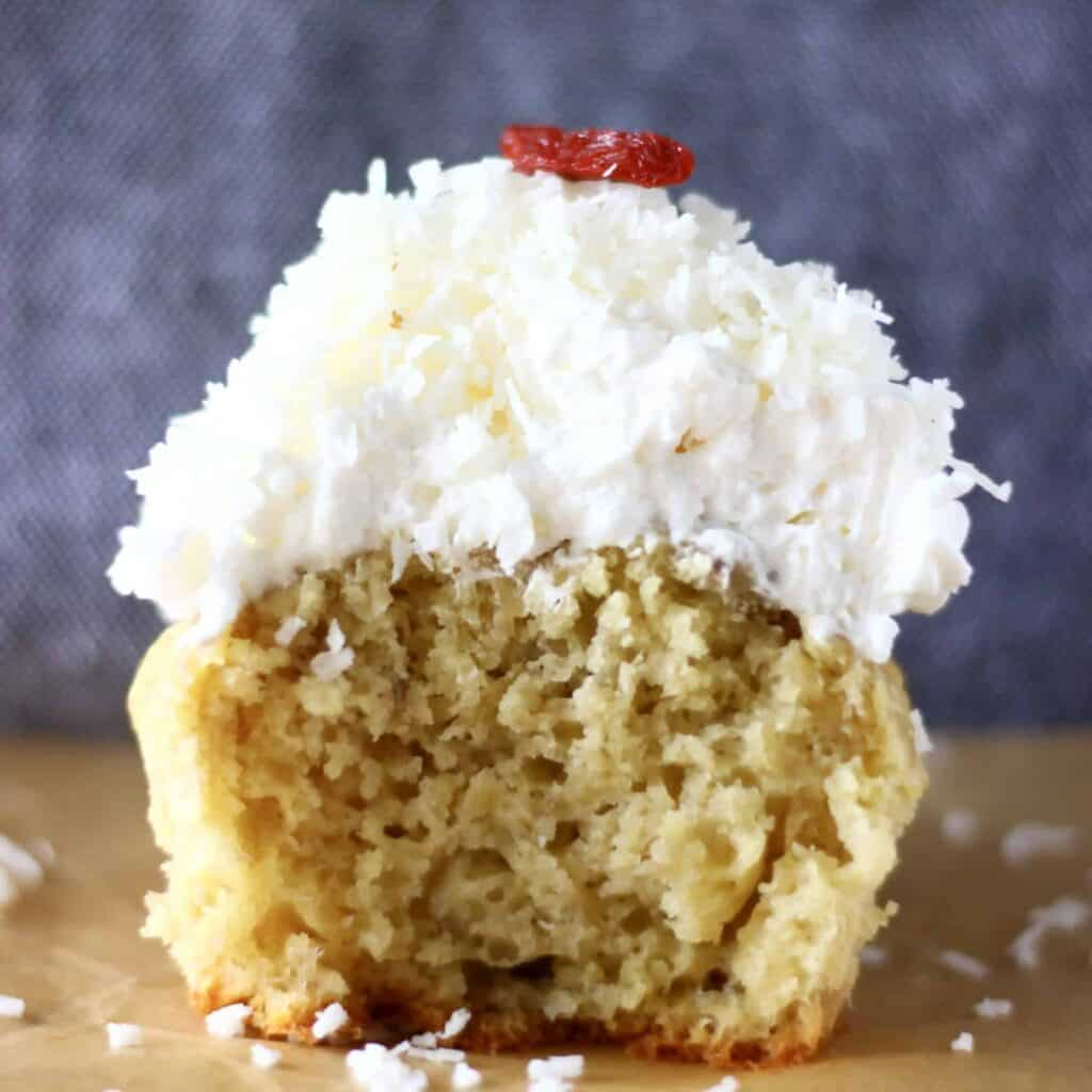 Photo of a cupcake topped with white frosting with a bite taken out of it against a grey background