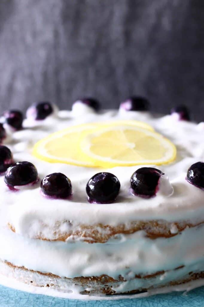 A white layer cake topped with lemon slices and blueberries shot from the side against a grey background