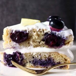 A slice of lemon blueberry layer cake against a grey background