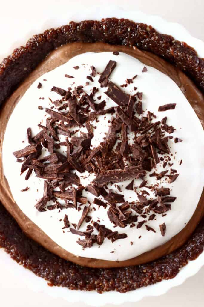 Chocolate pie topped with whipped cream and chocolate shavings in a white pie dish against a white background