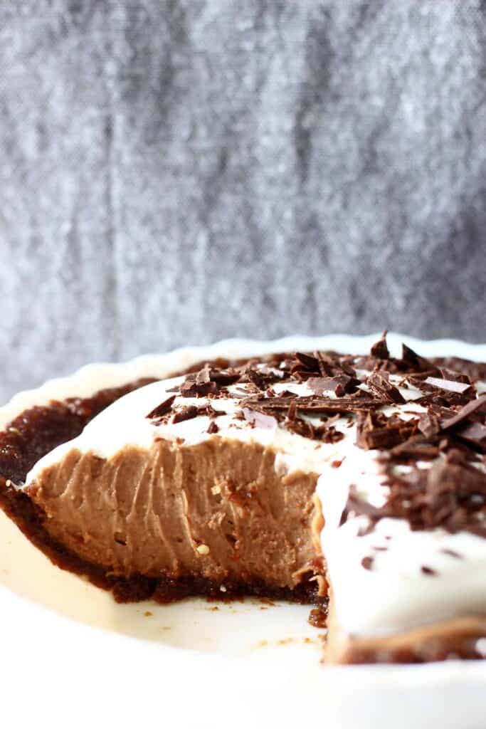 Chocolate pie in a pie dish against a grey fabric background with a slice cut out of it