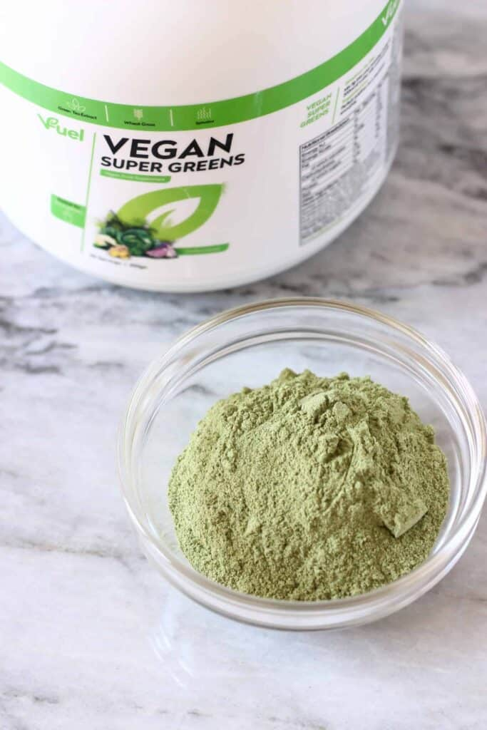 V Fuel Vegan Super Greens powder in a bowl with product package in the background.