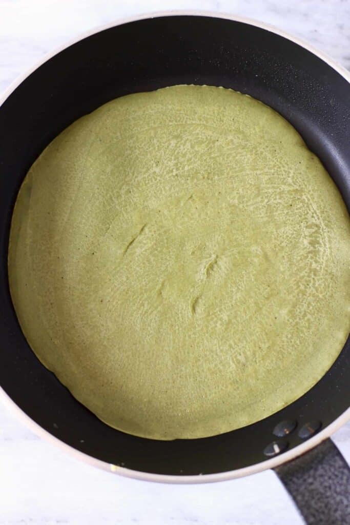 A round green-coloured wrap in a frying pan