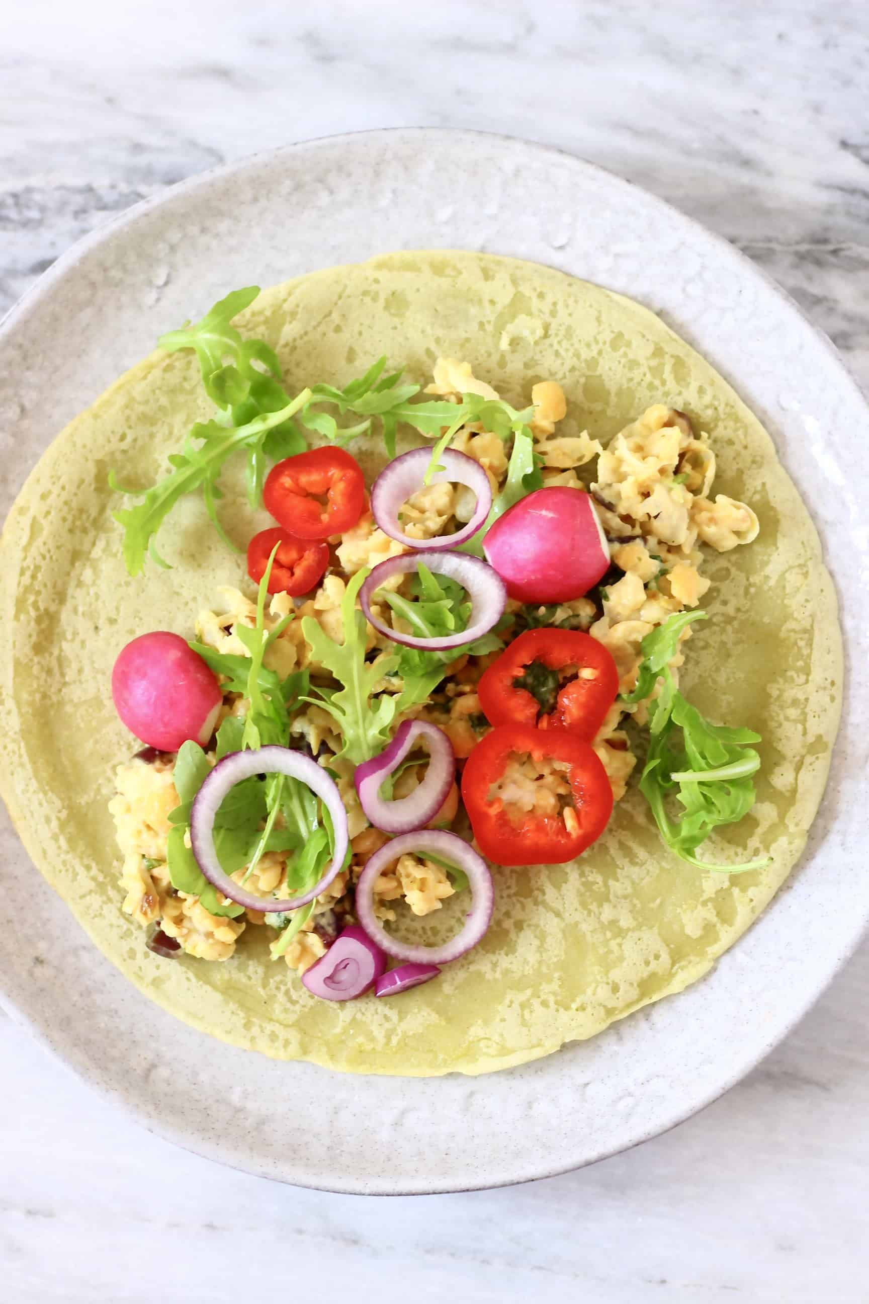 A green wrap on a plate, topped with chickpeas and salad