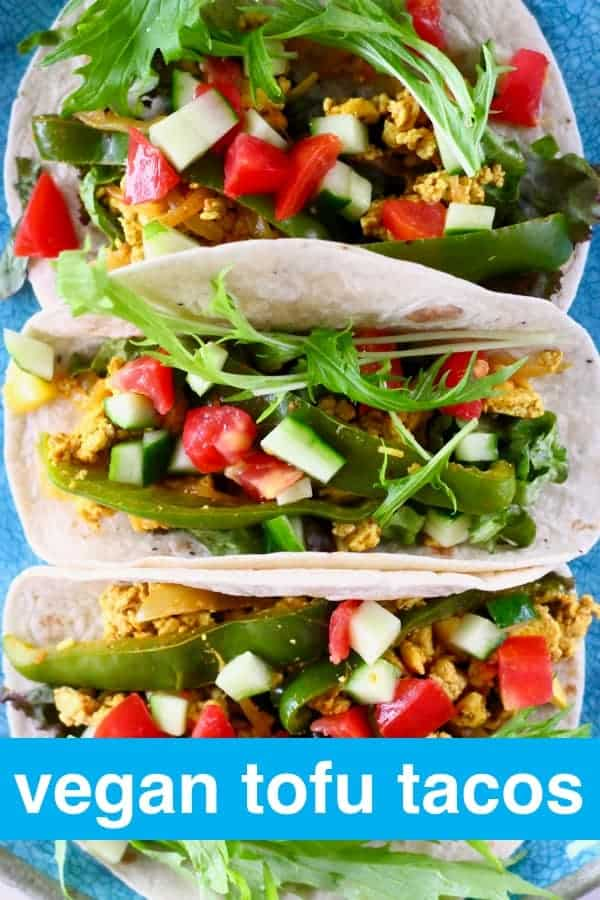 Close-up photo from above of three tacos filled with scrambled tofu, lettuce, cucumber and tomatoes