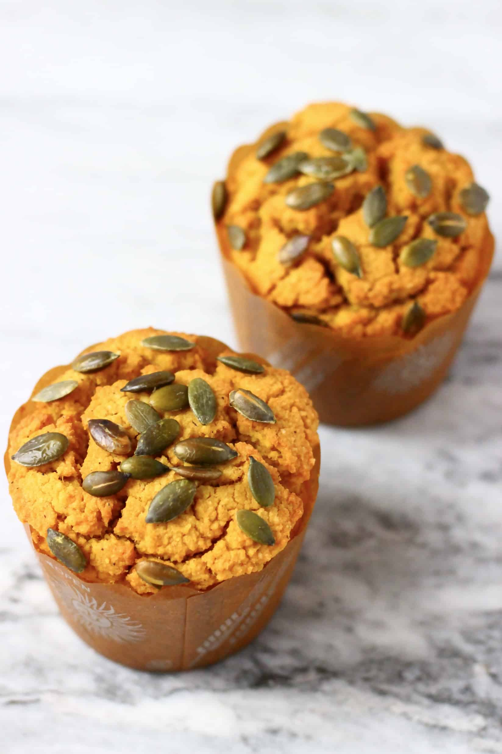 Two gluten-free vegan pumpkin muffins in muffin cases topped with pumpkin seeds