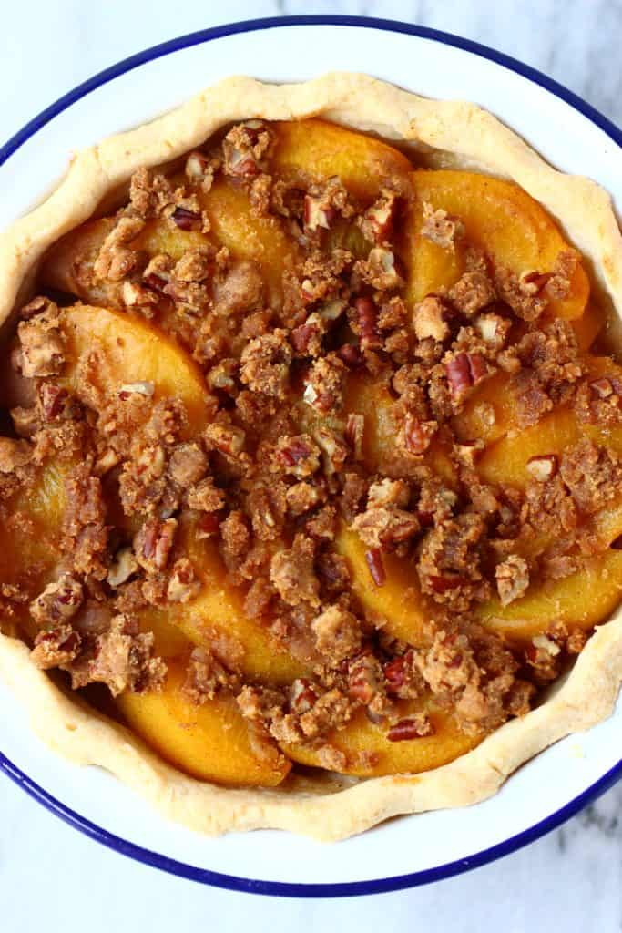 Photo of a peach pie with crumble topping in a pie dish taken from above