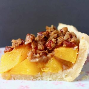 Photo of a slice of peach pie on a white plate with a gold fork and a grey background