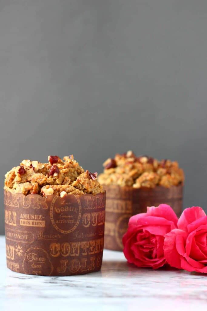 Photo of two brown muffins topped with pecan nuts in brown muffin cases on a marble slab with pink roses against a grey background