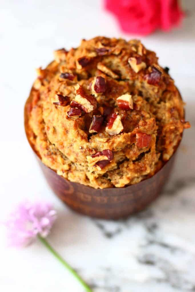Photo of a brown muffin in a muffin case topped with pecan nuts on a marble background with flowers