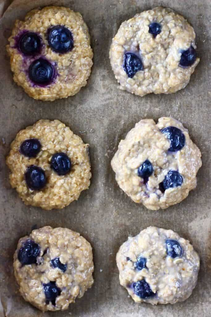 Six uncooked blueberry cookies on a brown piece of baking paper