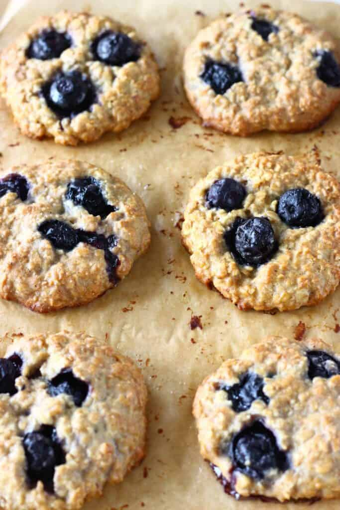 Six blueberry cookies on a brown piece of baking paper