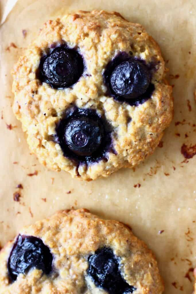 Two blueberry cookies on a brown piece of baking paper
