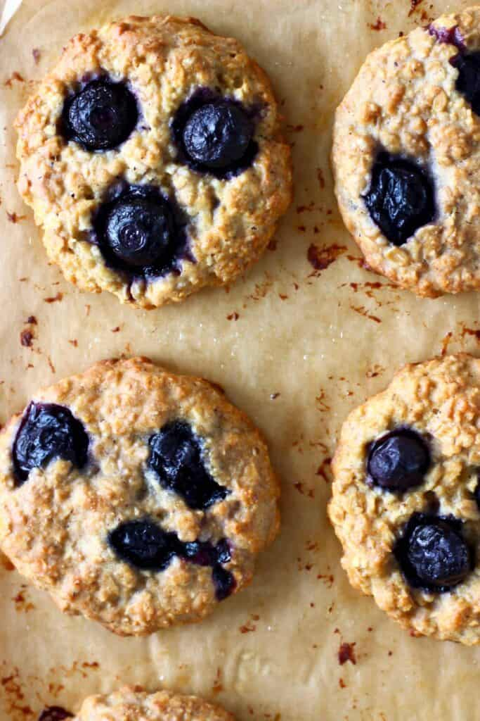 Four blueberry cookies on a brown piece of baking paper