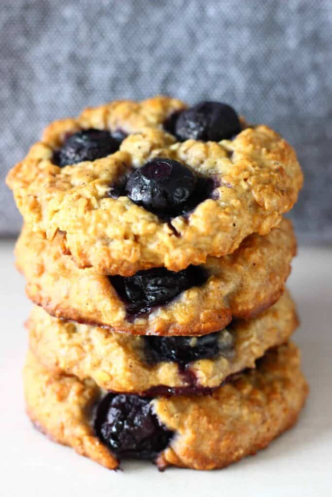Four blueberry cookies stacked up on top of each other against a grey background