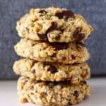 Photo of four chocolate chip cookies stacked up on top of each other against a grey background