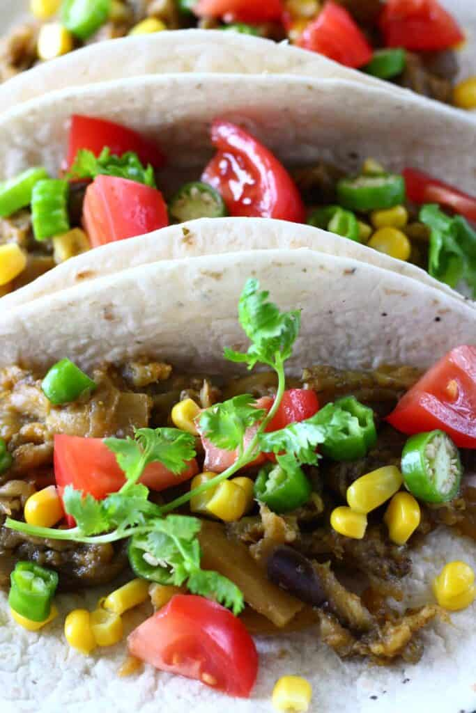 Photo of three tacos on a blue plate filled with roasted eggplant, sweetcorn, sliced green chilli, chopped tomatoes