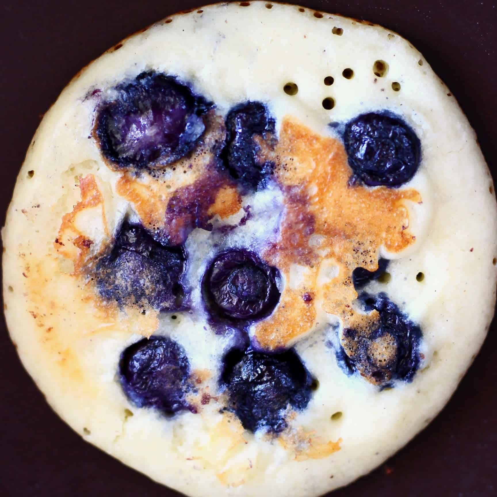 Photo of a blueberry pancake in a frying pan