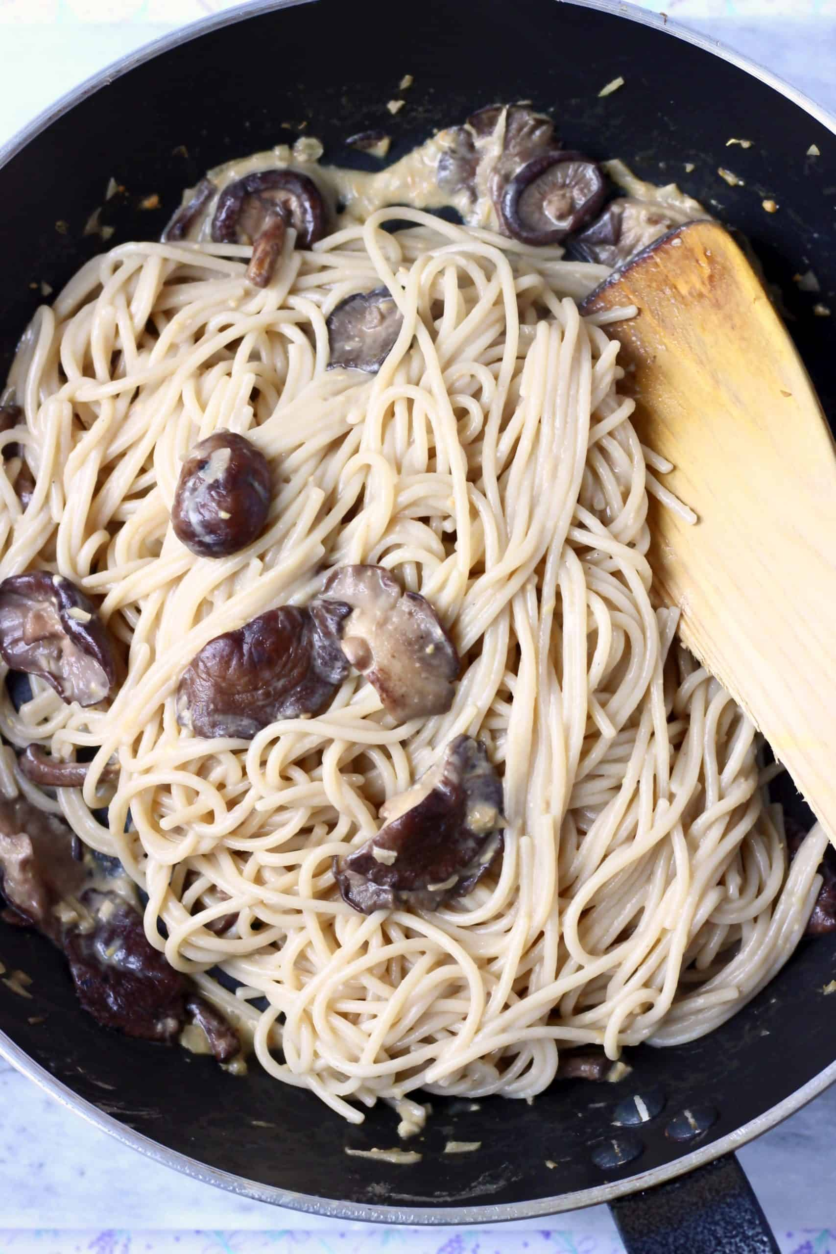 Creamy vegan miso pasta sauce with spaghetti and shiitake mushrooms being mixed together in a black frying pan