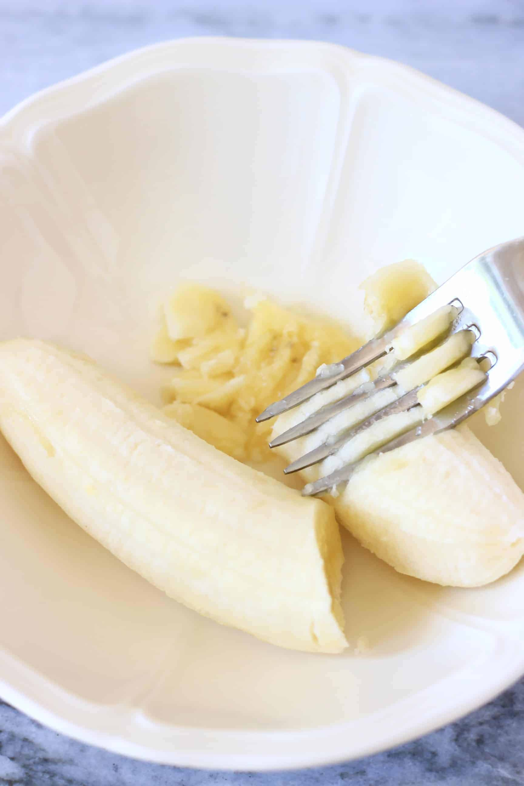 A small white bowl with a silver fork mashing a banana