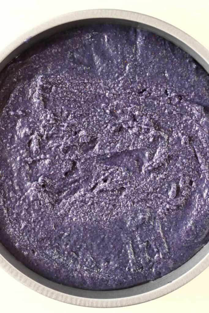 Photo of a deep purple cake batter in a silver baking tin against a white background