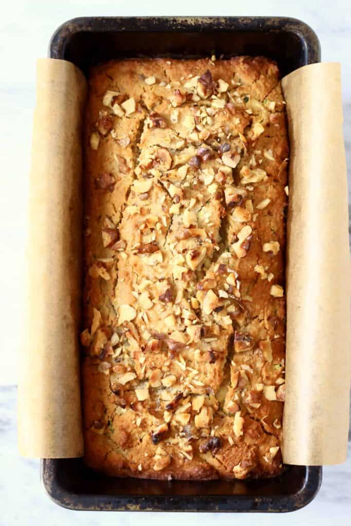 Photo of a black loaf tin with golden brown zucchini bread sprinkled with chopped walnuts against a marble background