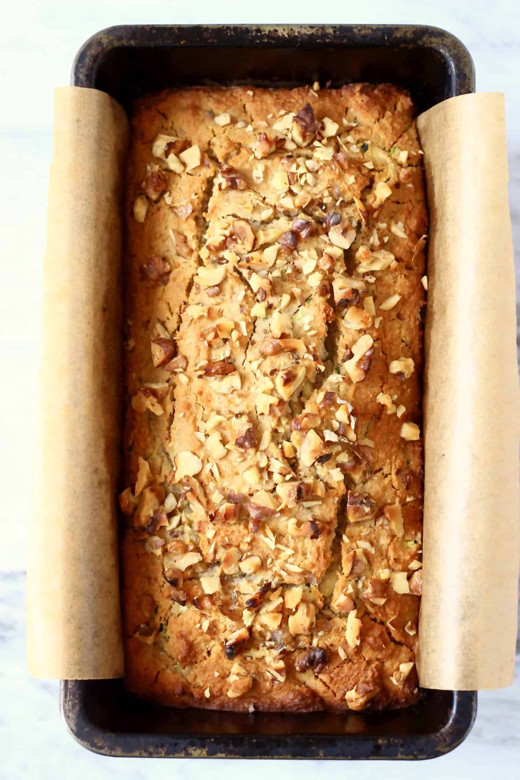 A loaf of gluten-free vegan zucchini bread in a loaf tin lined with baking paper