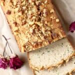 Photo of a loaf of zucchini bread with three slices against a sheet of brown baking paper with two red roses
