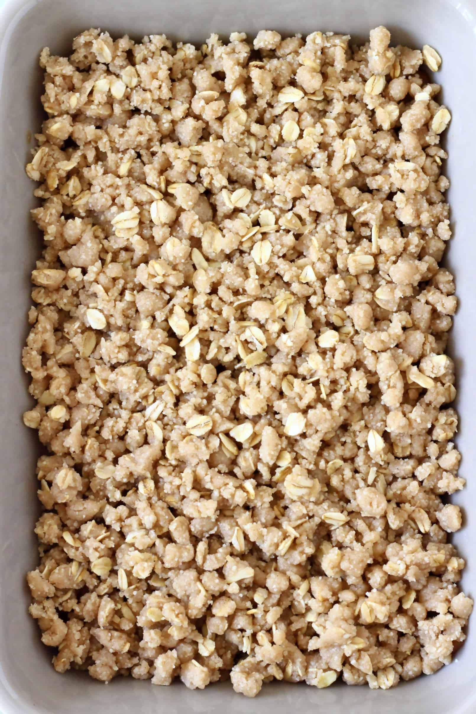 Raw gluten-free vegan crumble mixture with oats in a rectangular baking dish