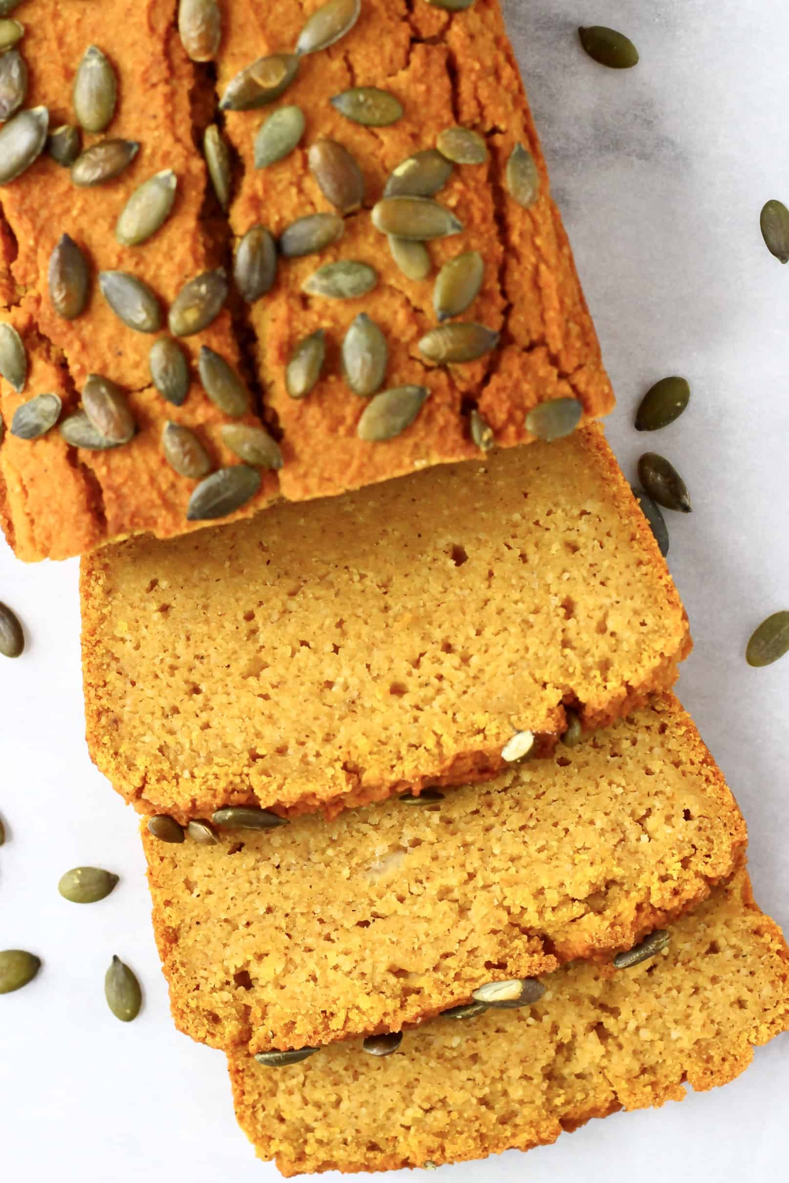 A loaf of gluten-free vegan pumpkin bread with three slices next to it