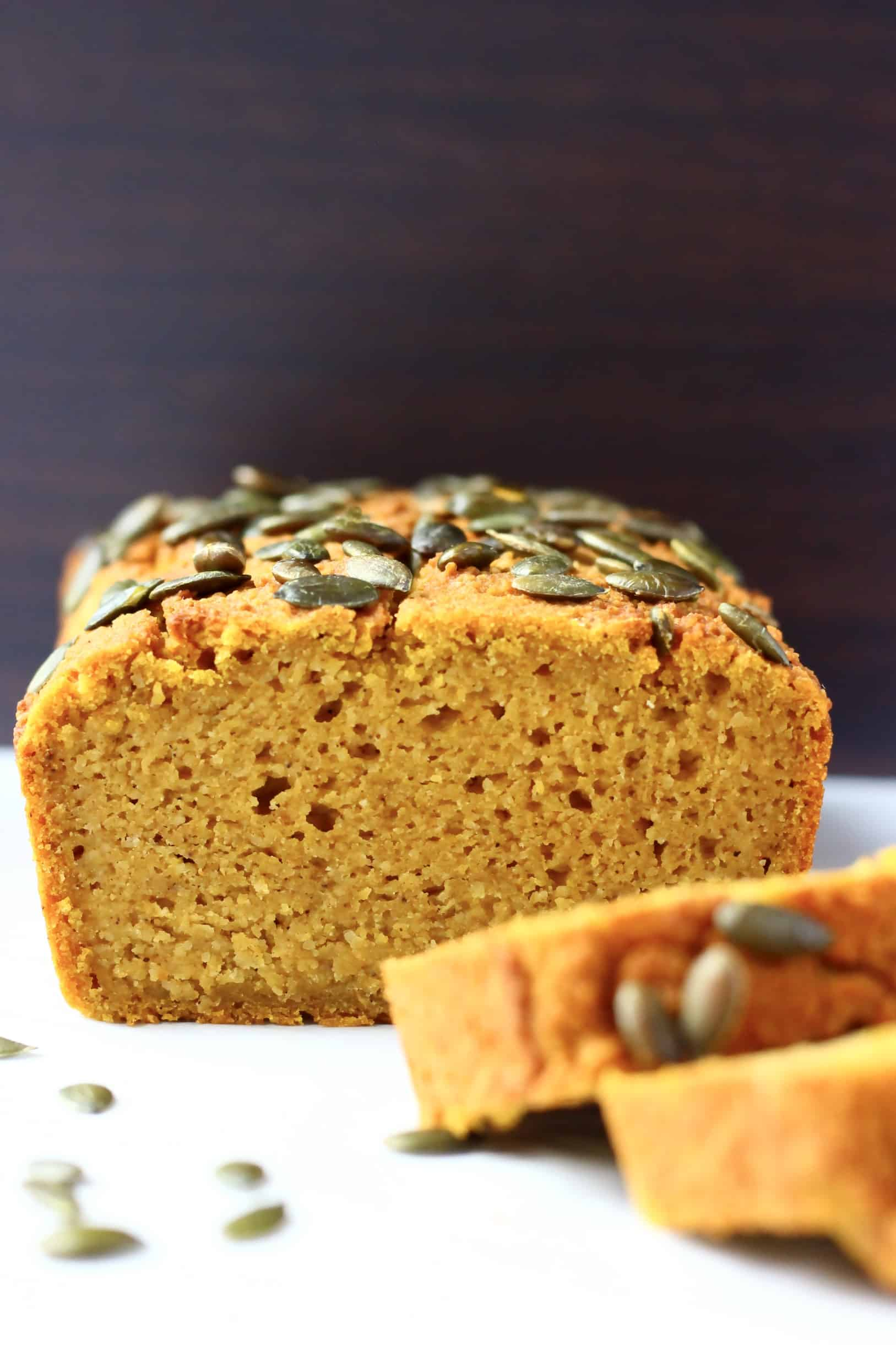 A sliced loaf of gluten-free vegan pumpkin bread topped with pumpkin seeds with two slices next to it