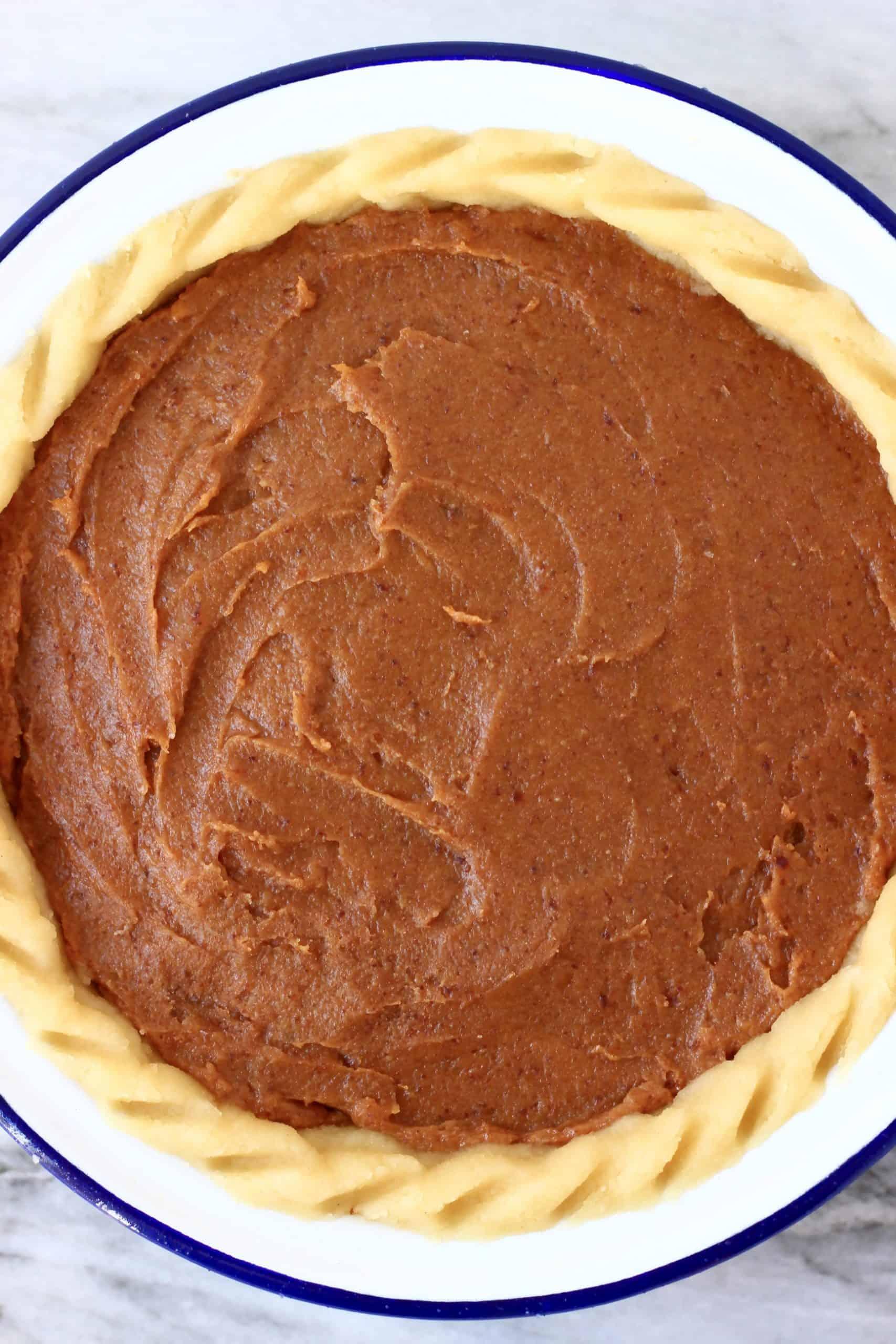 Pecan pie filling in a raw pie crust in a pie dish
