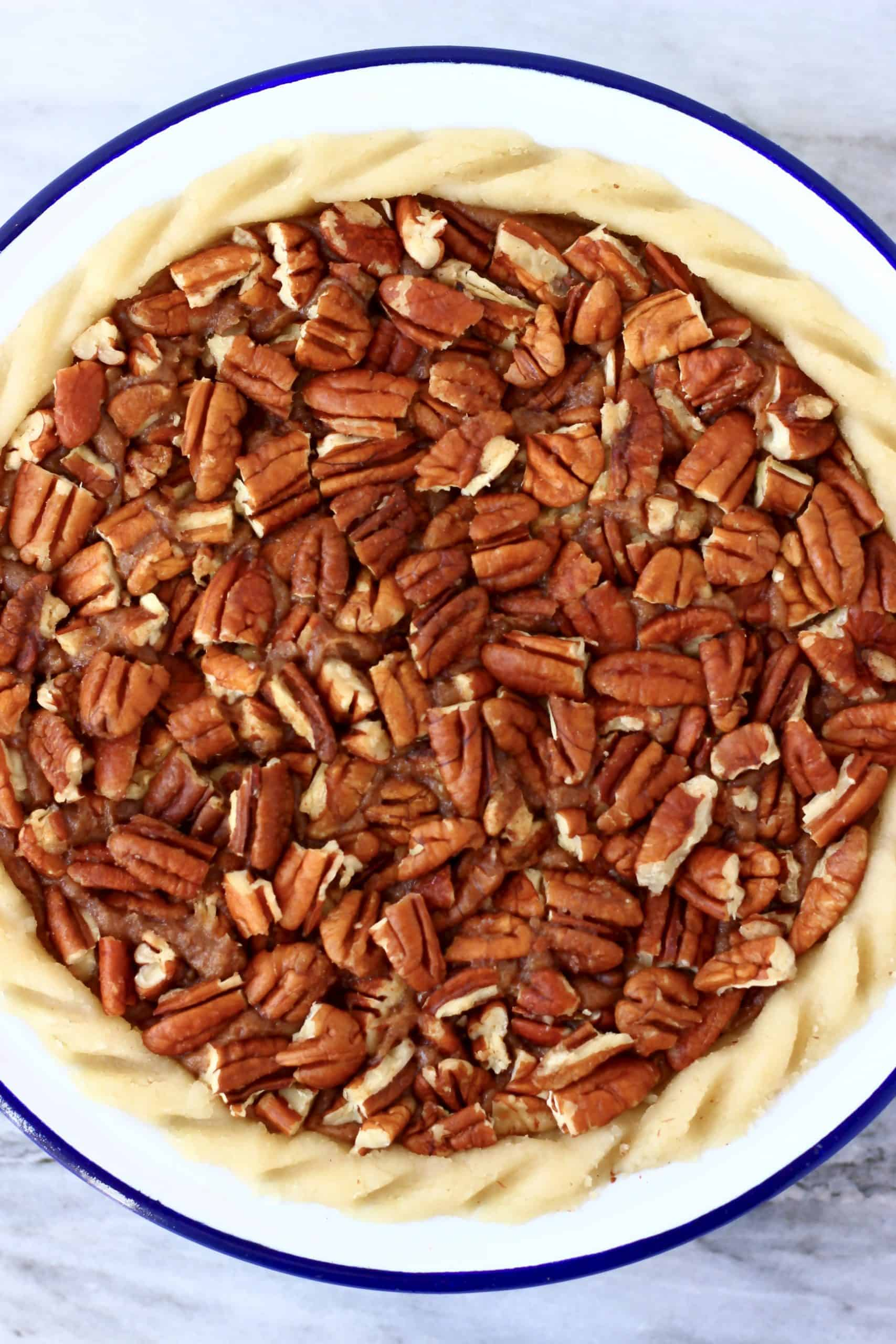 Raw gluten-free vegan pecan pie topped with chopped pecan nuts in a pie dish
