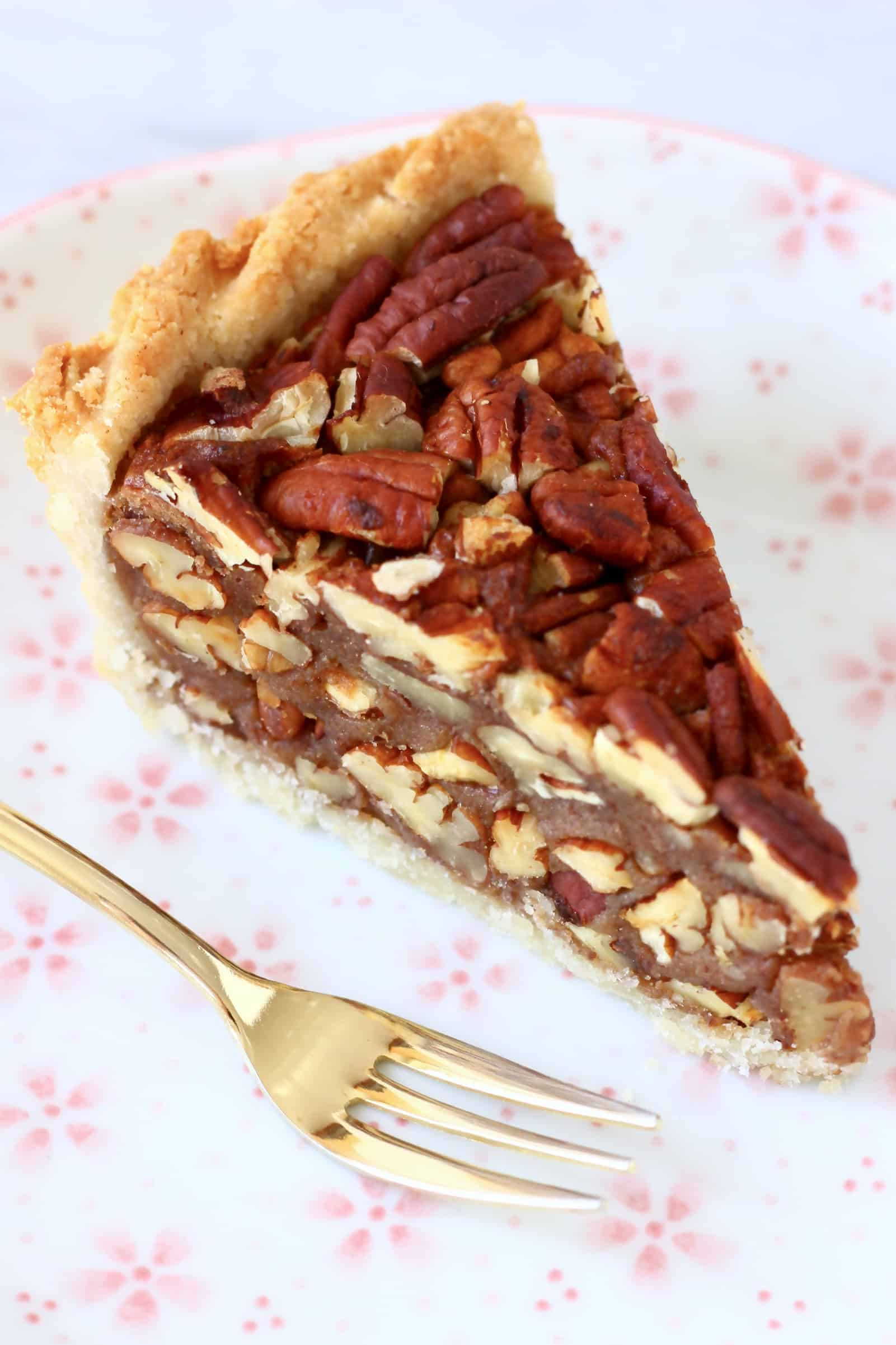 A slice of gluten-free vegan pecan pie on a plate with a gold fork