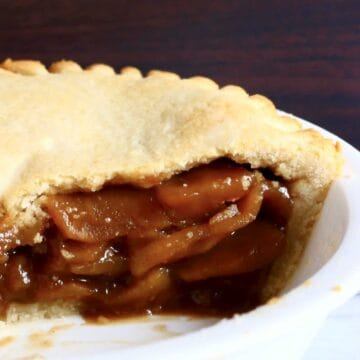 A sliced gluten-free vegan apple pie in a white pie dish