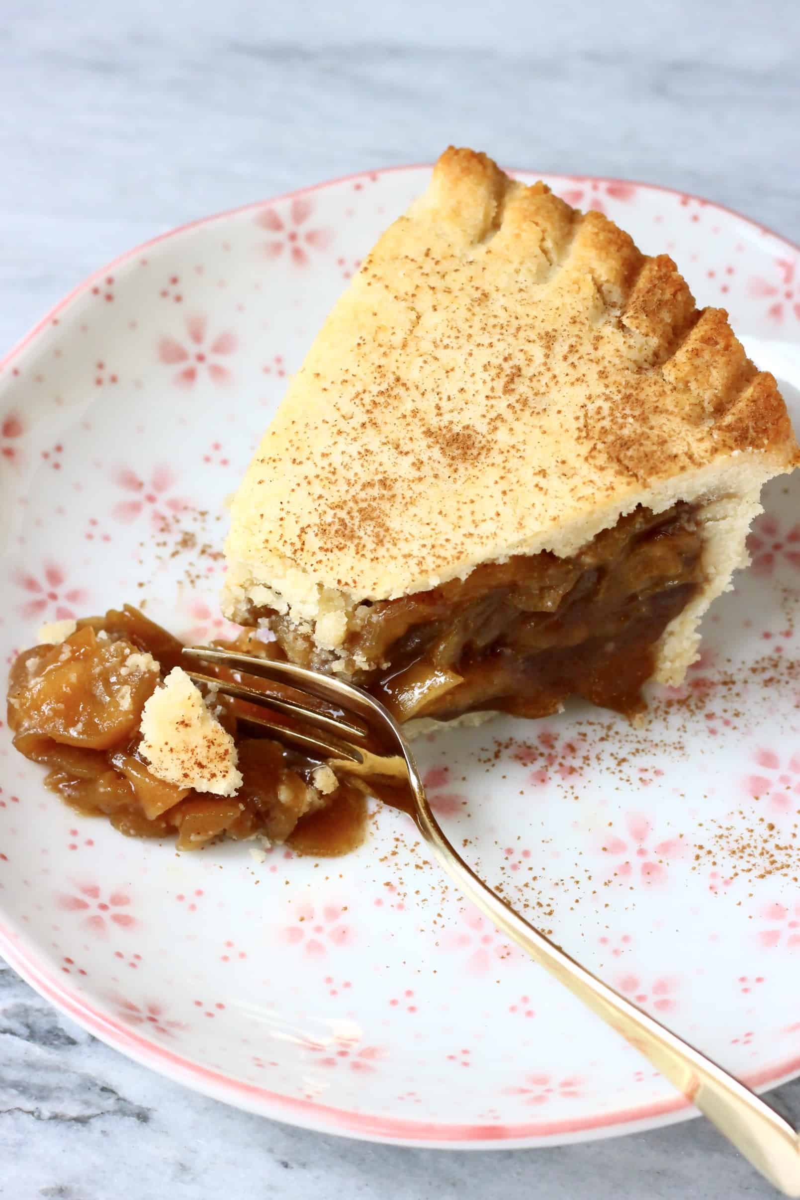 A slice of gluten-free vegan apple pie on a plate with a fork breaking off a piece