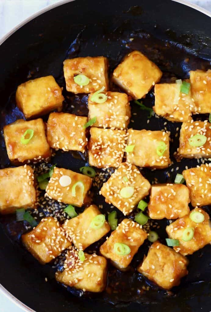 Photo of several pieces of fried tofu covered in sliced spring onions and sesame seeds in a black frying pan