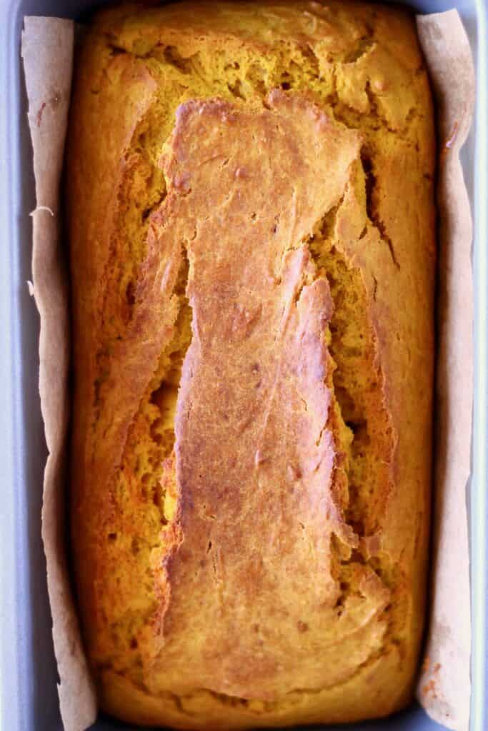 Photo of a loaf of pumpkin bread in a loaf tin lined with brown baking paper