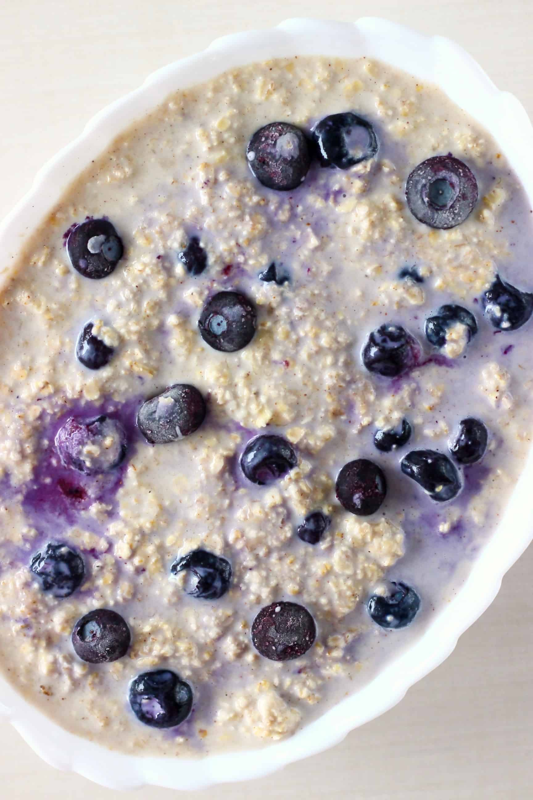 Raw vegan blueberry banana baked oatmeal mixture in a mixing bowl in a white oval baking dish