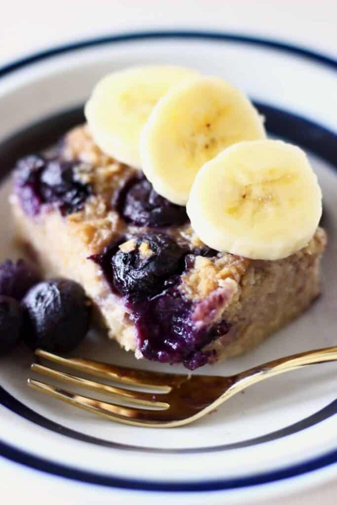 Photo of a square of baked oatmeal with blueberries topped with three banana slices in a white bowl with a blue rim and a gold fork