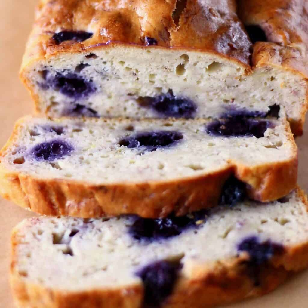 Photo of a blueberry loaf cake with two slices of it next to it
