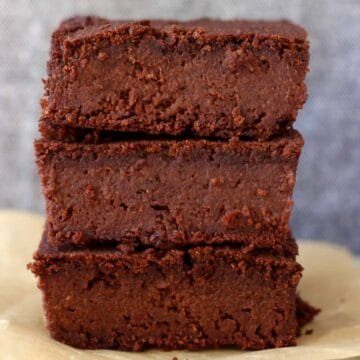 Three vegan black bean brownies stacked on top of each other against a grey background