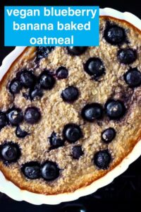 Photo of baked oatmeal with blueberries in a white oval dish against a black background