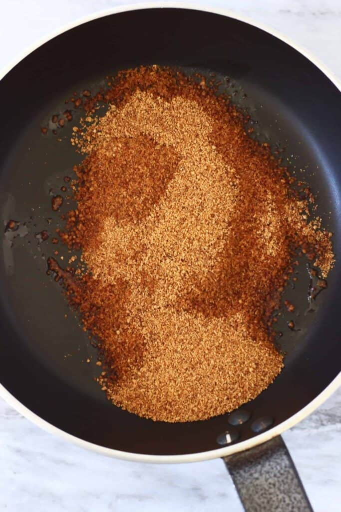 Photo of coconut sugar being melted in a black frying pan