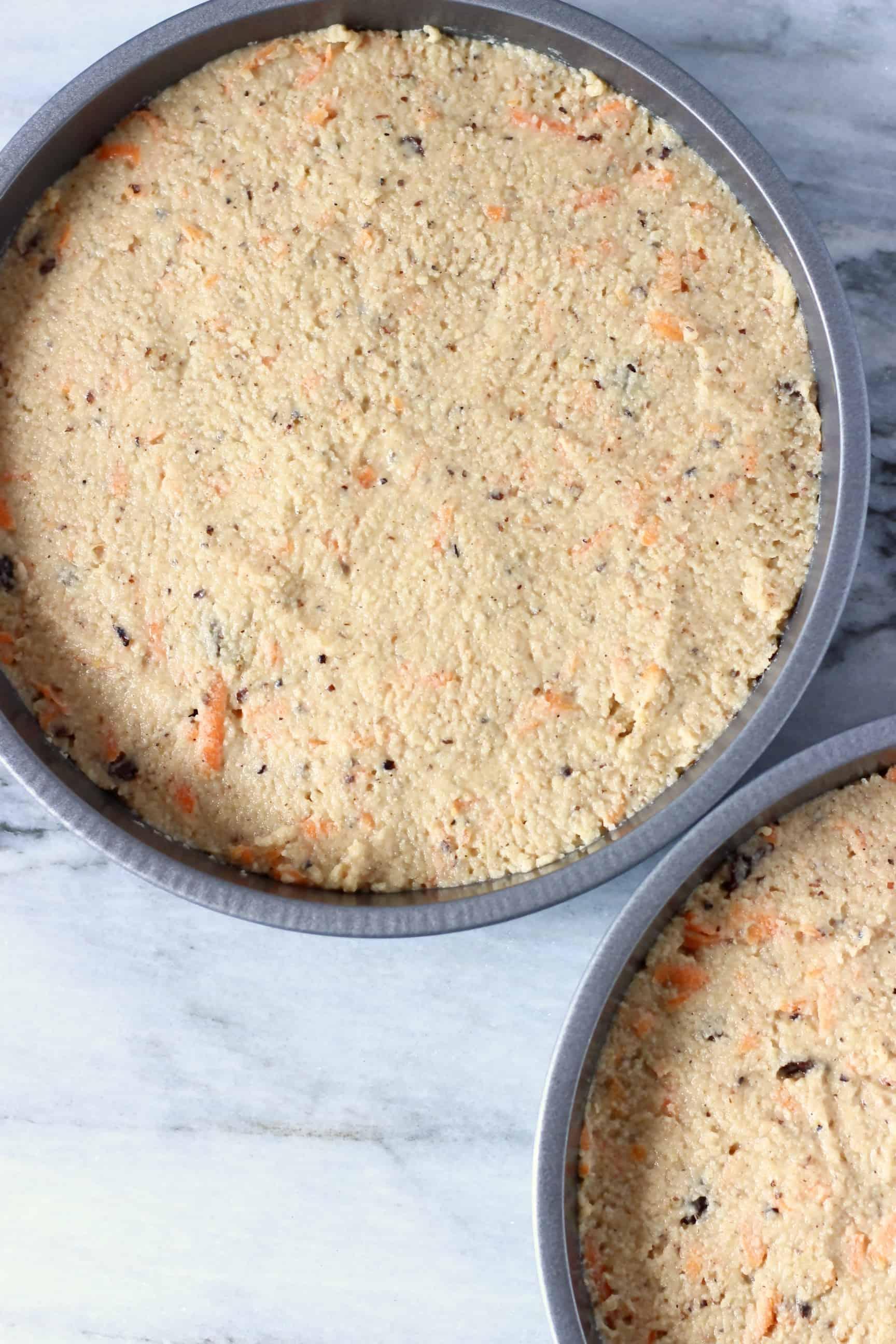 Two baking tins filled with raw vegan carrot cake batter