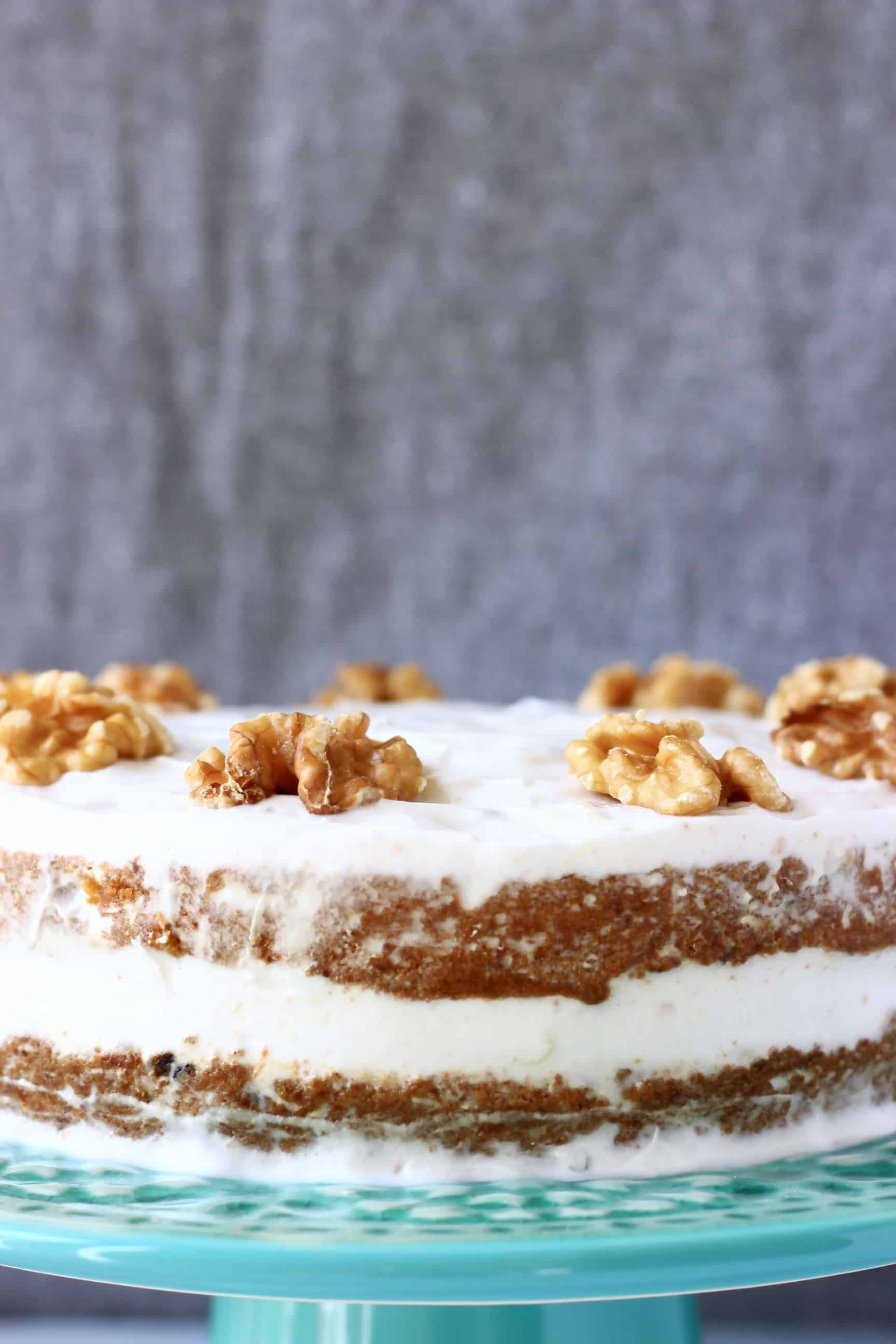 A vegan carrot cake covered in white frosting topped with walnuts against a grey background