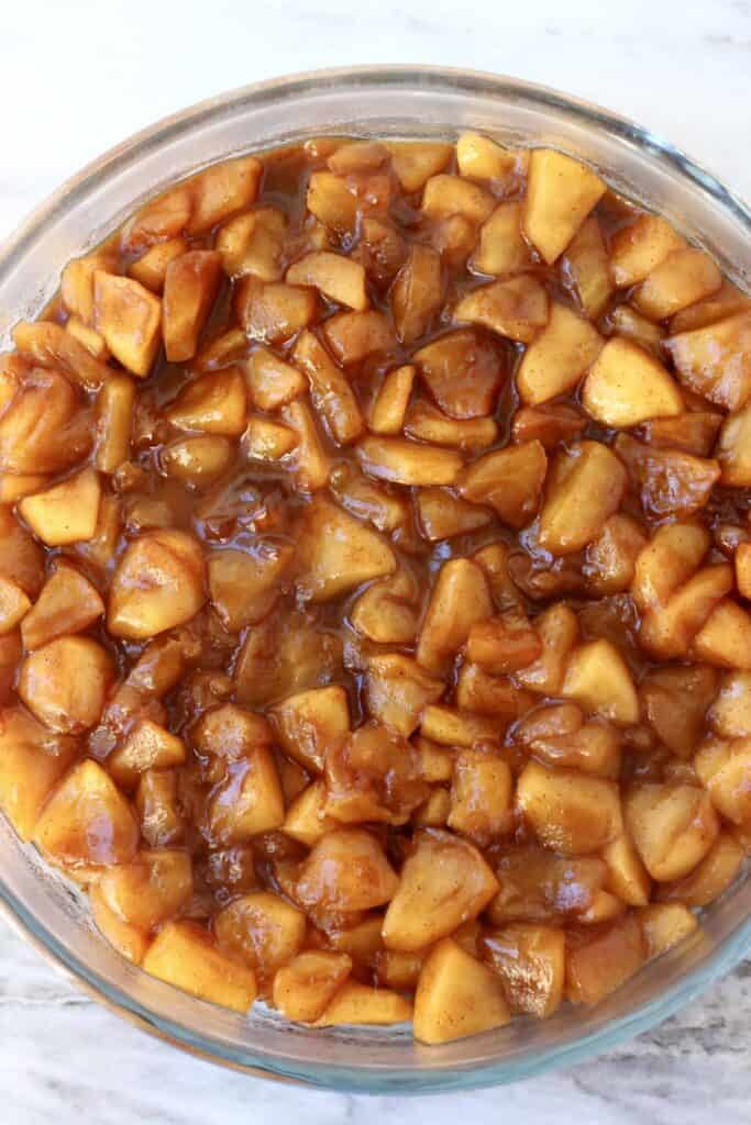 Photo of chopped apple pieces with cinnamon and brown sugar in a glass pie dish against a marble background